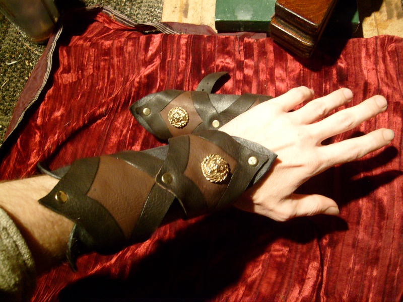 matched bracer set in rawhide leather and brass